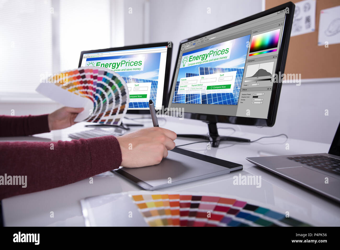 Side View Of A Young Male Designer Holding Colorful Swatch Working On Computer In Office - Stock Image