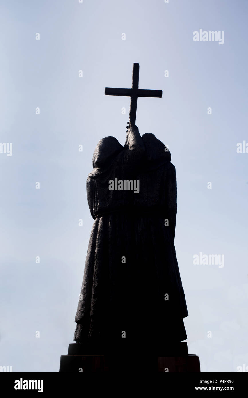 Dark silhouette of sculpture, two monks holding a Christian cross. Concept of power of Christian religion and pilgrimage. - Stock Image