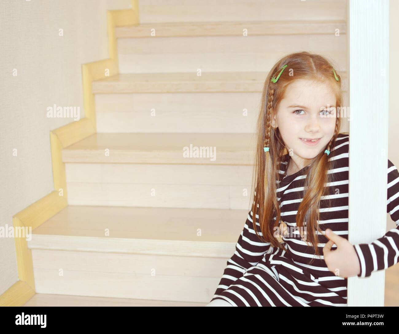 Blond child, girl 7-9 years old, standing on the stairs and smiling, closeup portrait, copy space - Stock Image