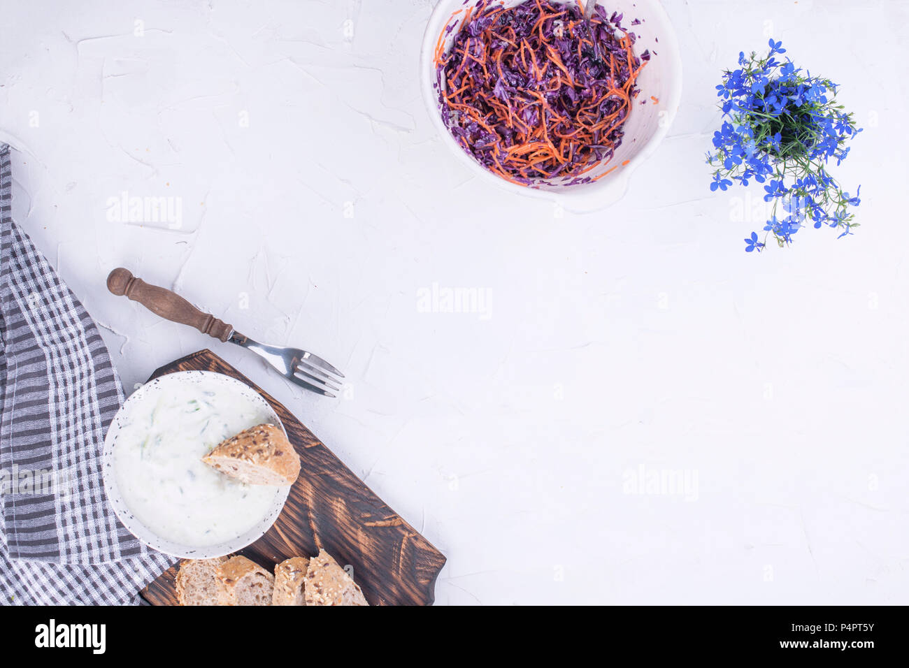 Salad from fresh cabbage and carrots, fresh bread and yogurt with cucumber. Spring vegetables and white sauce. Lunch is vegetarian. Tasty and healthy food. Copy space - Stock Image