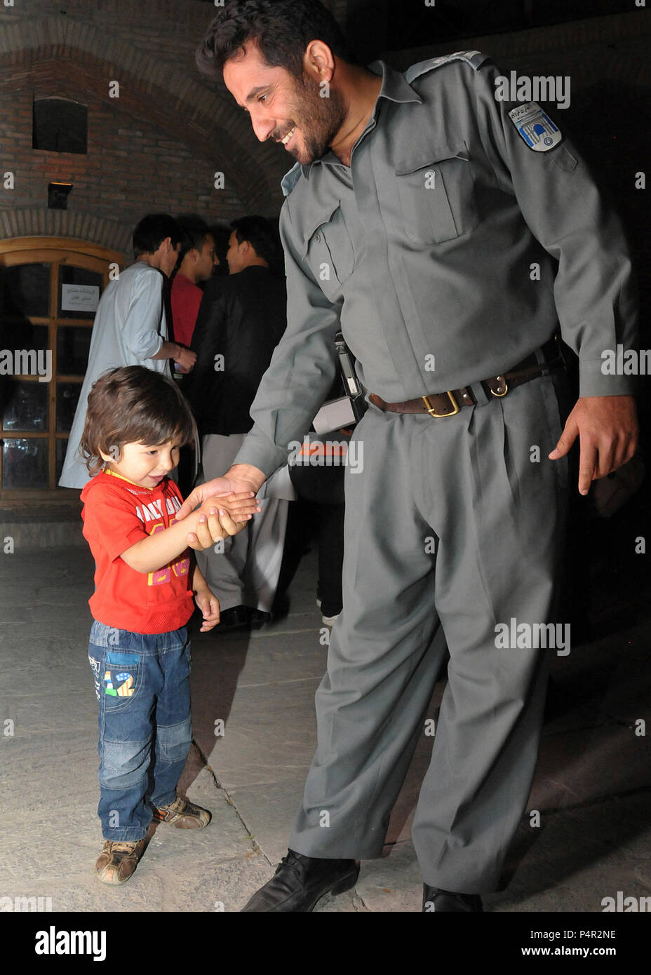 KABUL -- (May 21, 2012) An Afghan National Police officer slaps hands with an Afghan child during the 1st Police Film Festival held at the Babur Gardens, May 21.  The week-long festival was designed to open a cultural dialogue between the ANP and Afghan community that will help improve communication and aid in shaping new, positive perceptions of the Afghan police force.  U.S. Navy - Stock Image