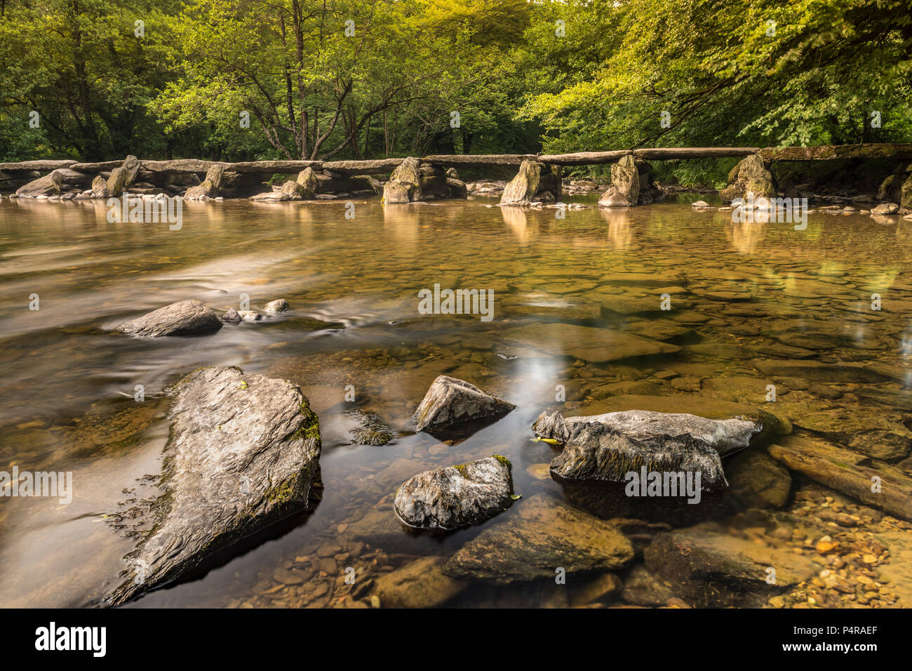 UK Weather -June 21st, the longest day, the wind strengthens at dawn clearing the cloud allowing the sun to light up the historic Tarr Steps on the Ri - Stock Image