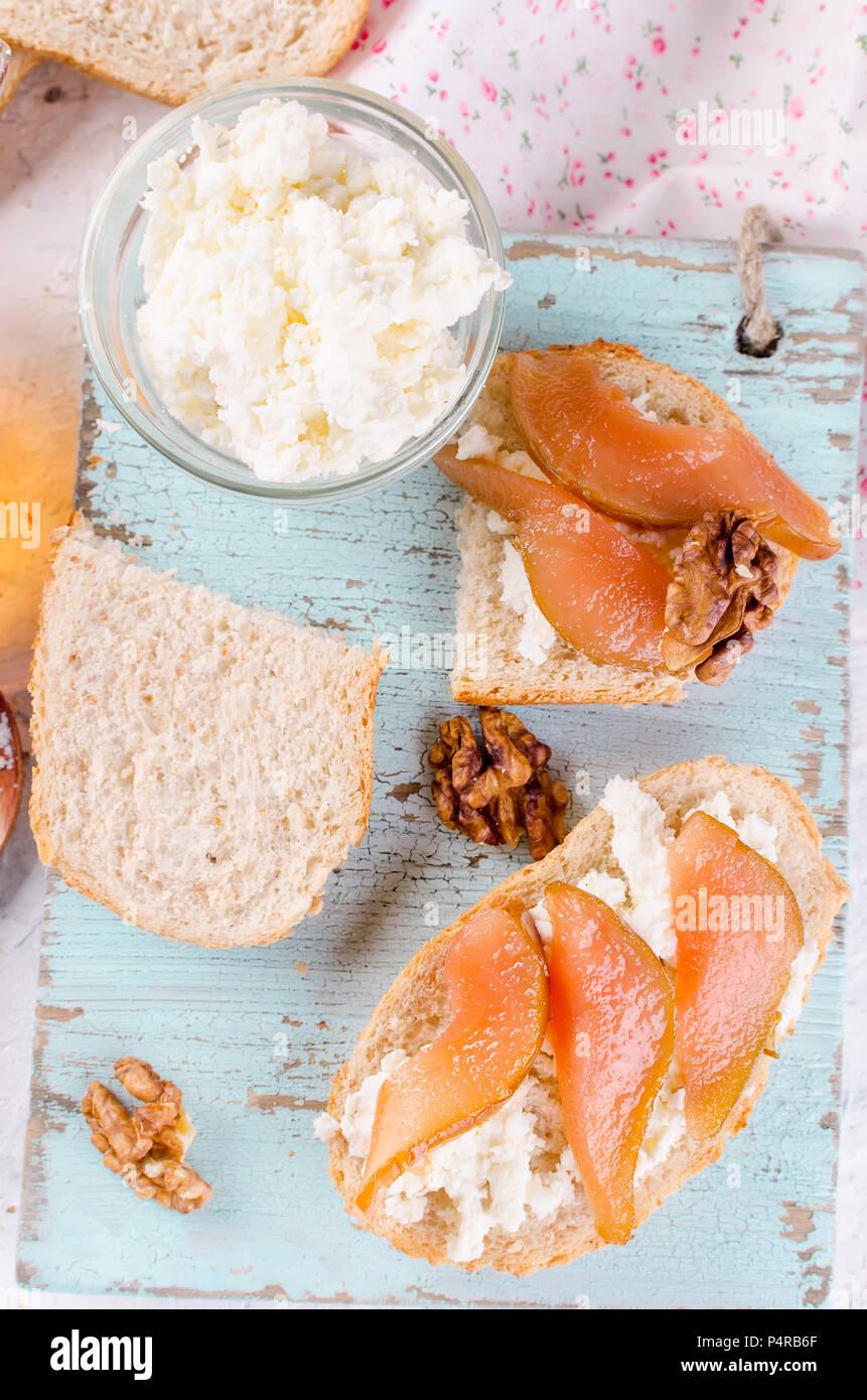 Breakfast set. tea with sandwiches with ricotta cheese and pear jam.   Cup of tea and glass teapot. Top view, copy space - Stock Image