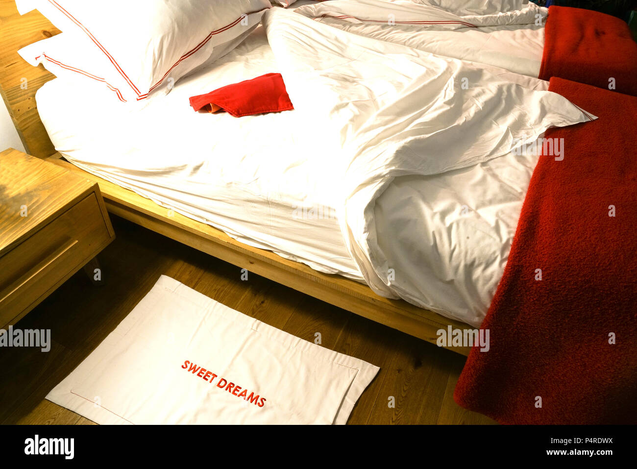 Double bed pulled back with ruffled untidy sheets with red hotwater bottle waiting. - Stock Image