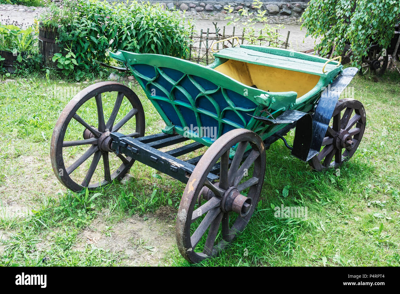 An old carriage for trips in a harness with a horse stands on the green grass Stock Photo