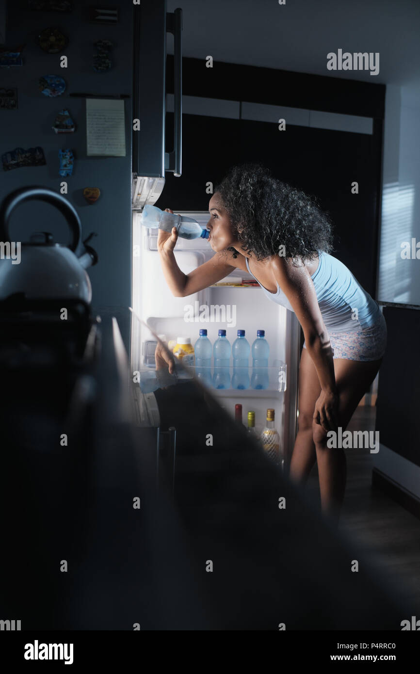 Black Woman Sweating And Drinking Water At Night - Stock Image