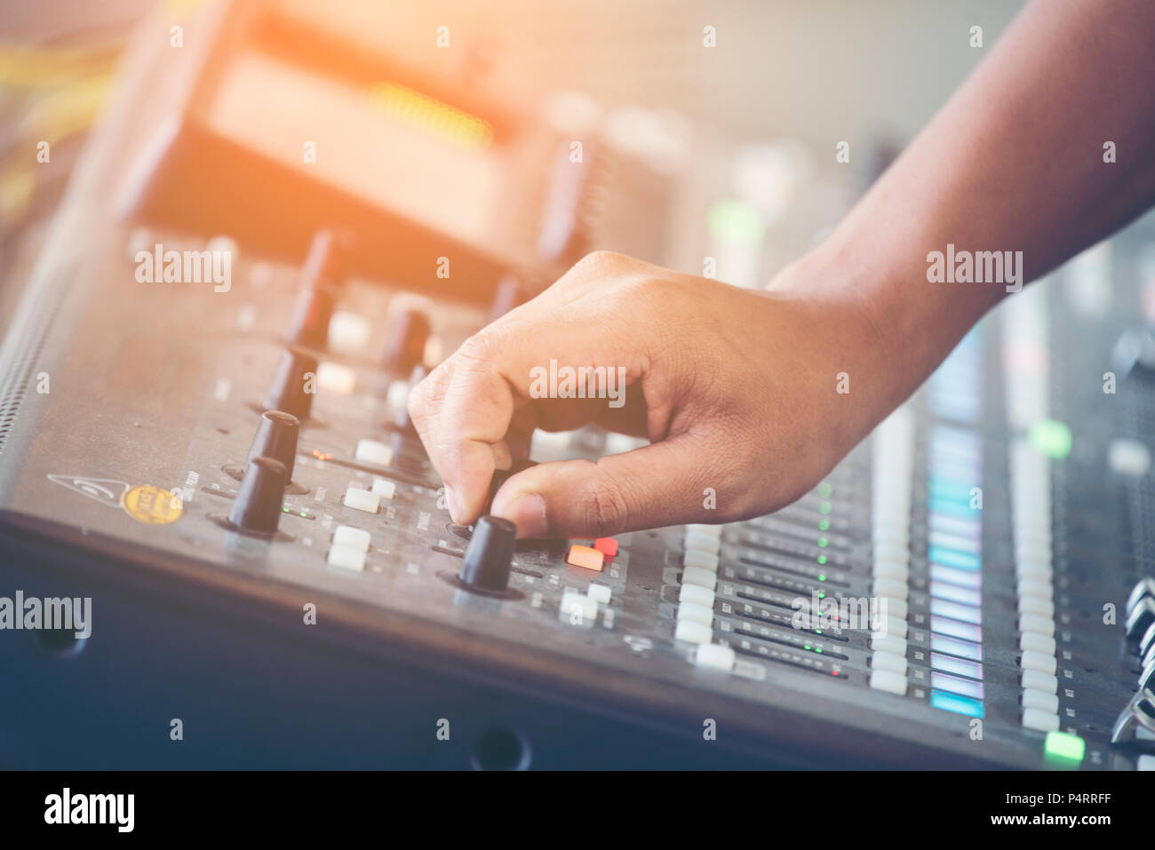 professional stage sound mixer closeup at sound engineer hand using audio mix slider working during concert performance - Stock Image