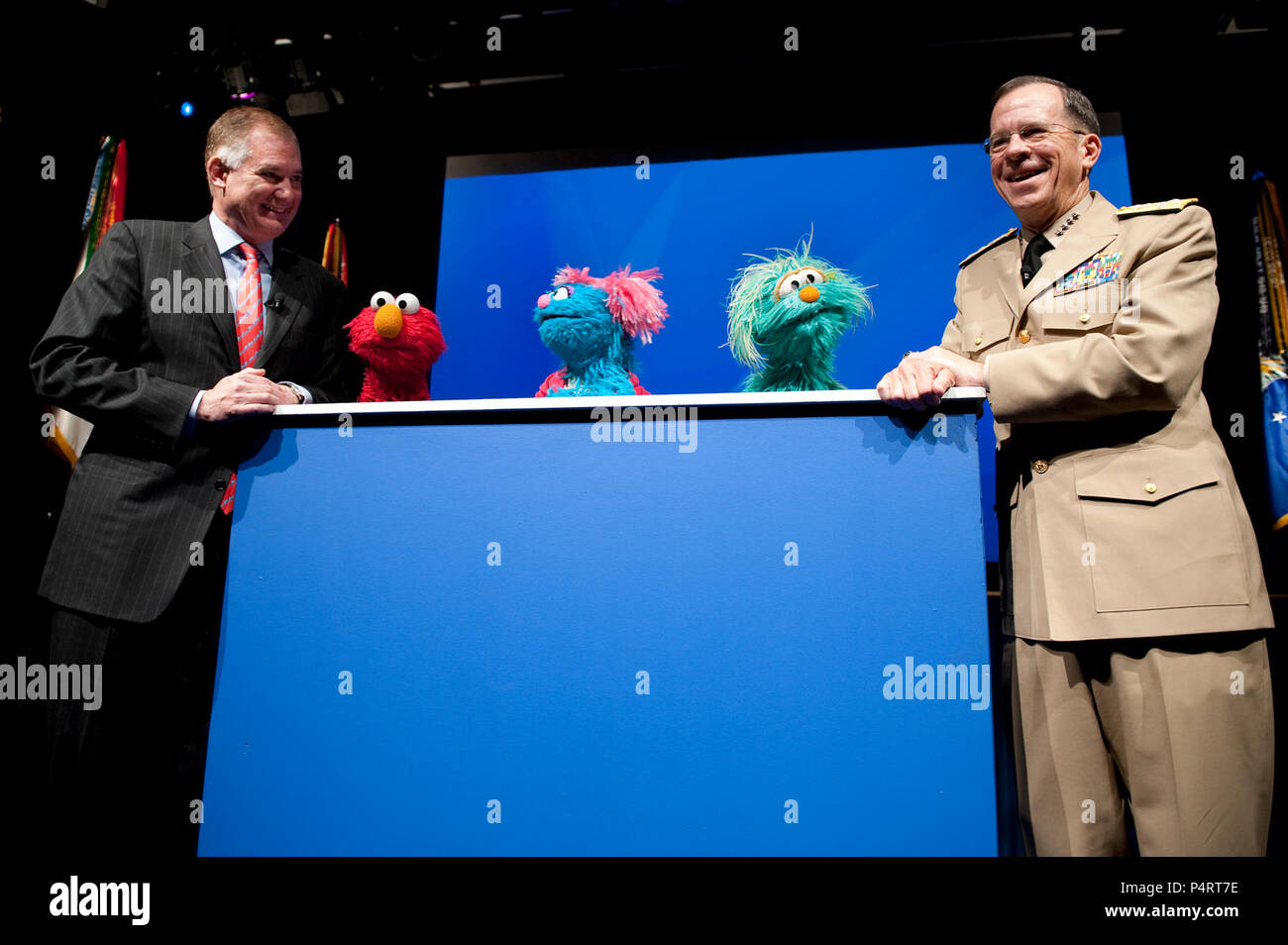 Deputy Secretary of Defense William J. Lynn, left, and Chairman of the Joint Chiefs of Staff Navy Adm. Mike Mullen help Sesame Street muppets Elmo, Jesse and Rosita host a preview of the PBS special 'When Families Grieve' at the Pentagon April 13, 2010. The program features several families coping with the loss of a parent and the skills that help them move forward. (DoD - Stock Image