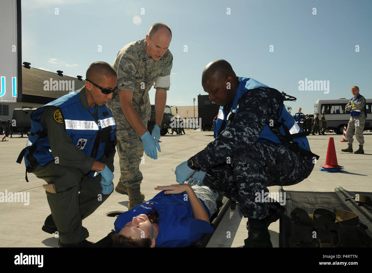 U.S. Navy Lt. Sung Choi, left, Air Force Capt. Robert Watson and Hospital Corpsman 2nd Class Chamunorwa Chimhau perform triage on a mock accident casualty during a major accident response exercise on Misawa Air Base in Japan Sept. 8, 2010. The joint, bilateral exercise with the U.S. Navy, U.S. Air Force and Japanese Air Self-Defense Force is designed to improve interoperability in the event of a major catastrophe. (DoD - Stock Image