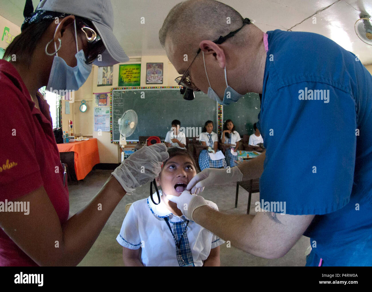 U.S. Navy Cmdr. Bradley J. Smith, right, a dentist, examines a patient before extracting a tooth during a dental and civic action project at San Miguel National High School in San Miguel, Philippines. Oct. 6, 2010. Smith is deployed for Cooperation Afloat Readiness and Training, which is a bilateral exercise held annually in Southeast Asia to strengthen relationships and promote maritime security. (DoD - Stock Image