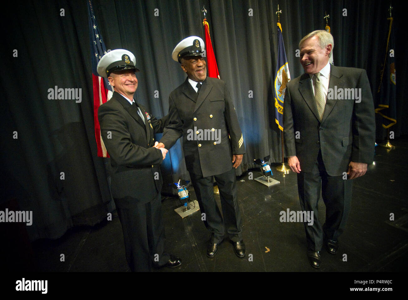 Master Chief Petty Officer of the Navy Rick West, left, and Secretary of the Navy Ray Mabus congratulate Honorary Chief Hospital Corpsman Bill Cosby, center, during his pinning ceremony at the Navy Memorial in Washington, D.C., Feb. 17, 2011. (DoD Stock Photo
