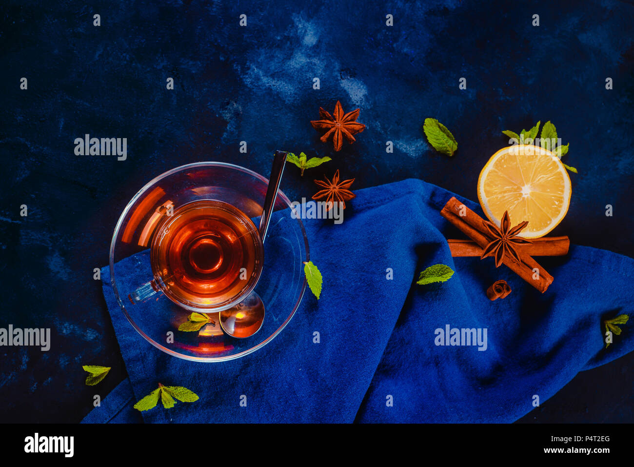 Hot drink header with glass teacup, linen napkin, lemon slices, cinnamon, anise stars and mint leaves on a dark background. Dark food photography flat Stock Photo