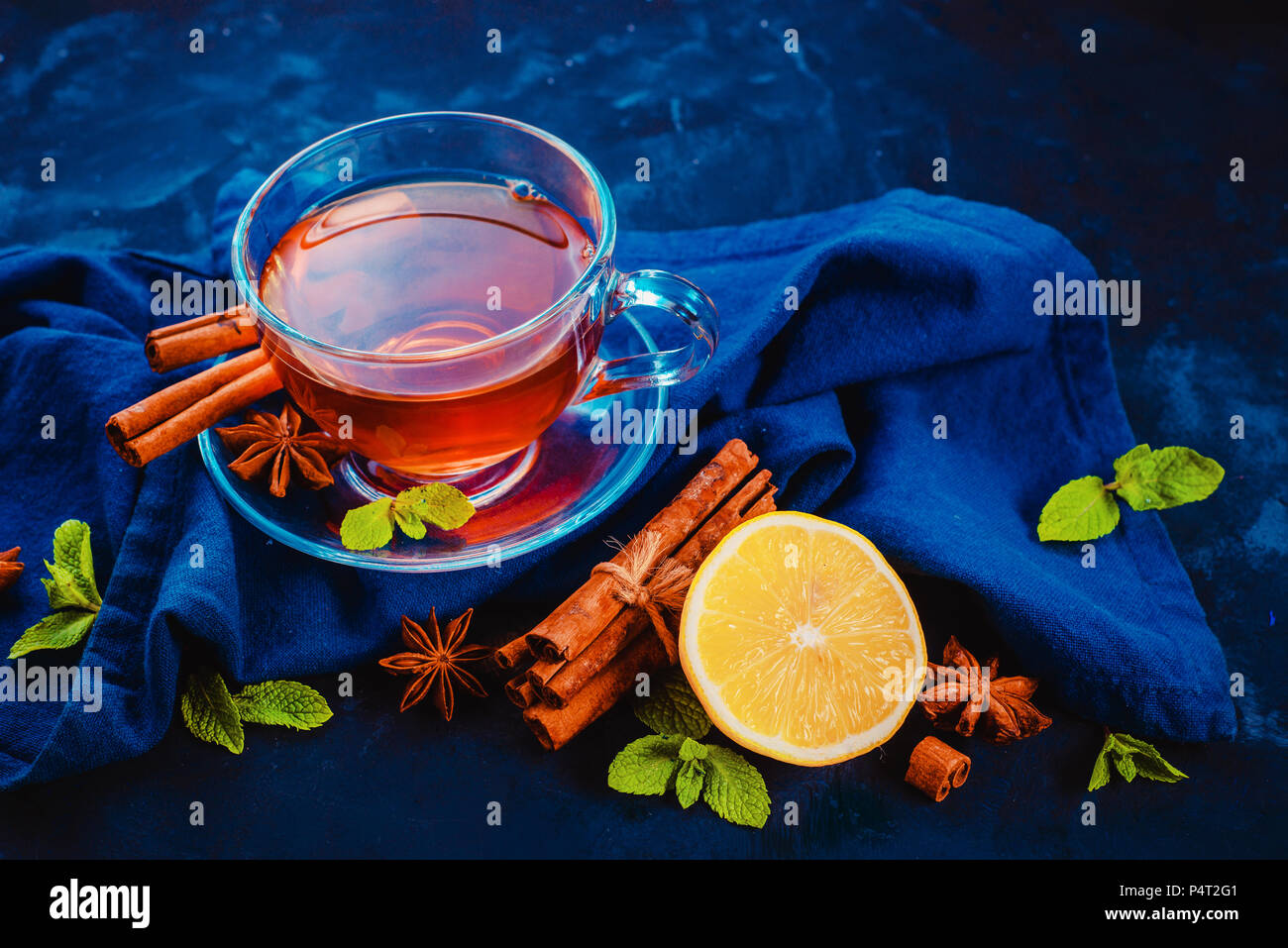 Glass tea cup and saucer with lemon slices, cinnamon, anise stars and mint leaves on a dark background with linen napkin. Vibrant colors hot drink fla - Stock Image