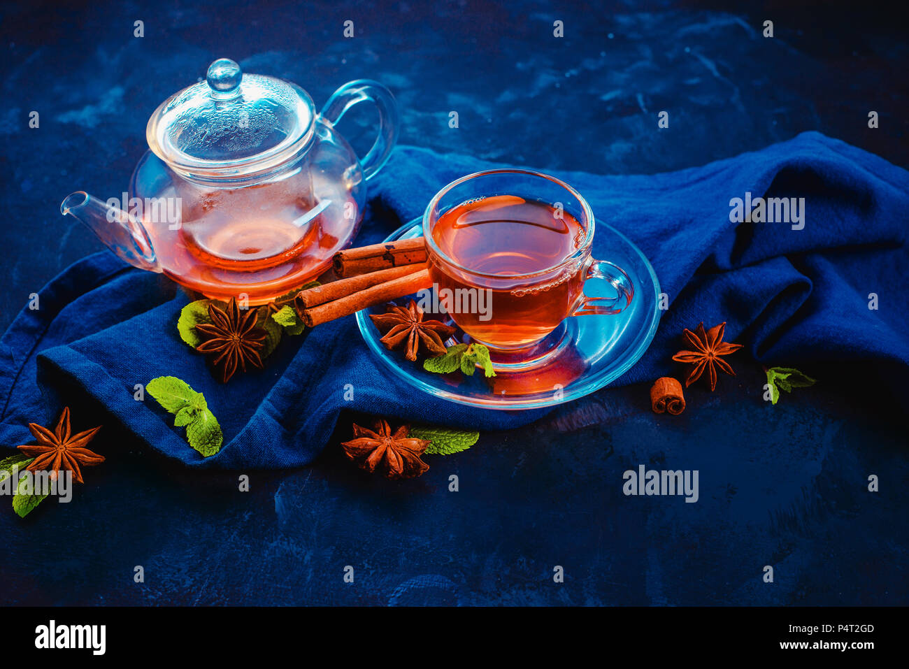 Black tea in a glass cup and a tiny teapot with lemon slices and mint leaves on a dark background. Vibrant colors hot drink header with copy space. - Stock Image