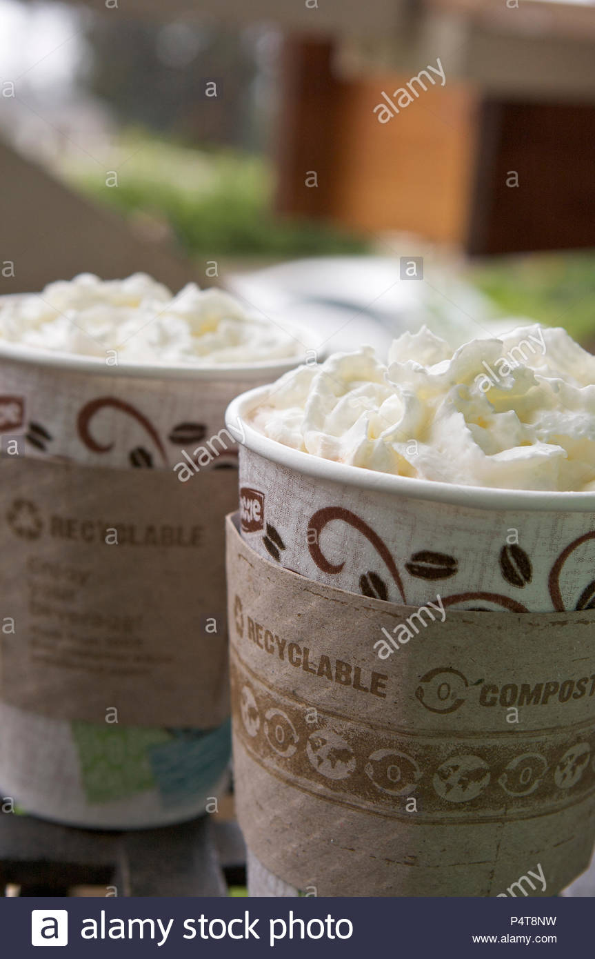 Coffee with whipped cream in eco-friendly cups. - Stock Image
