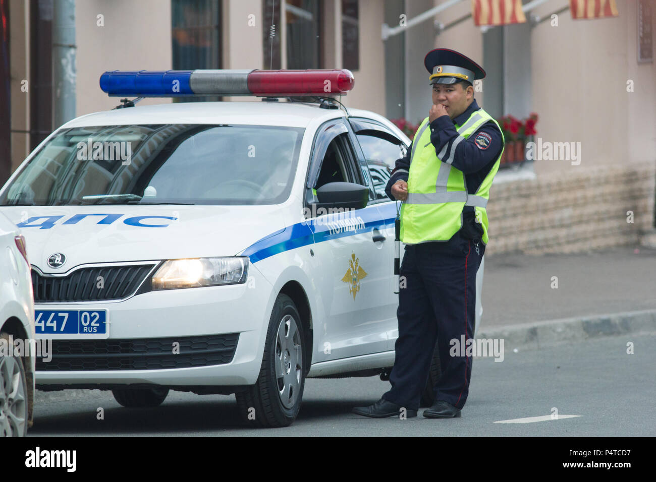 KAZAN, RUSSIA - JUNE 21, 2018: Traffic policeman standing near company car at the street - Stock Image