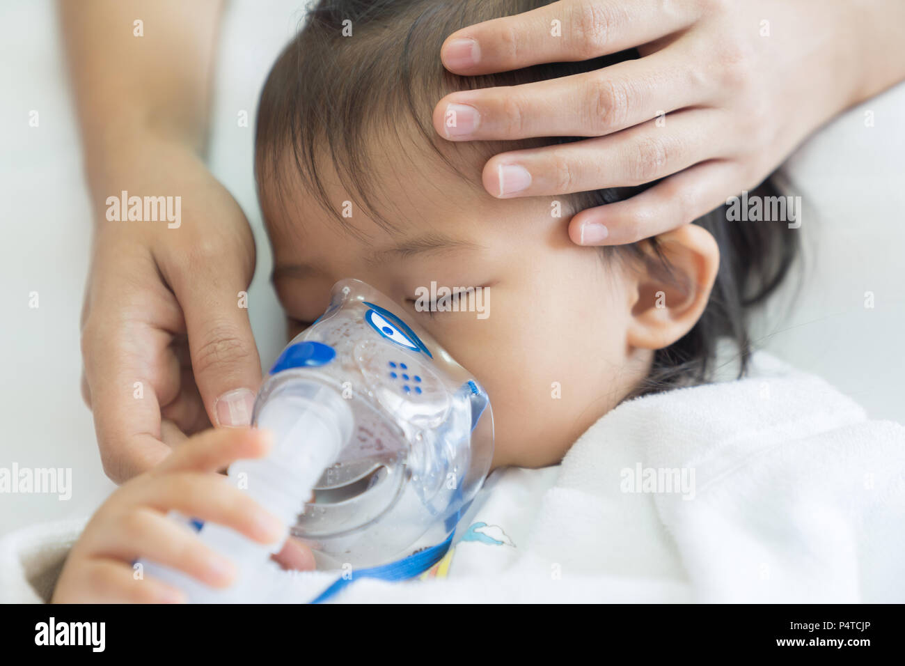 Asian baby girl breathing treatment with mother take care, at room hospital, close up health care kid concept sunny light background. Stock Photo