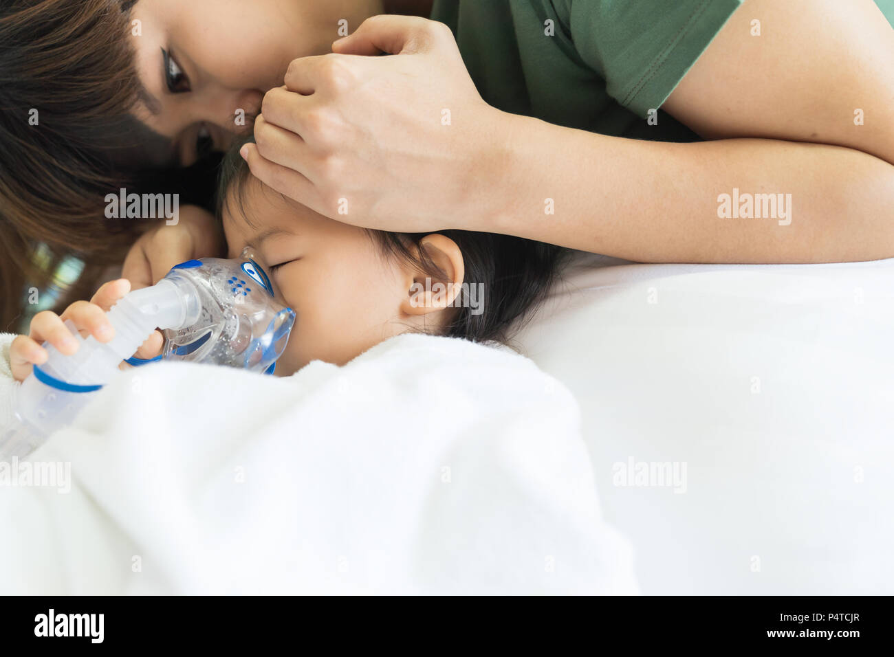 Asian baby girl breathing treatment with mother take care, at room hospital, close up health care kid concept sunny light background. - Stock Image