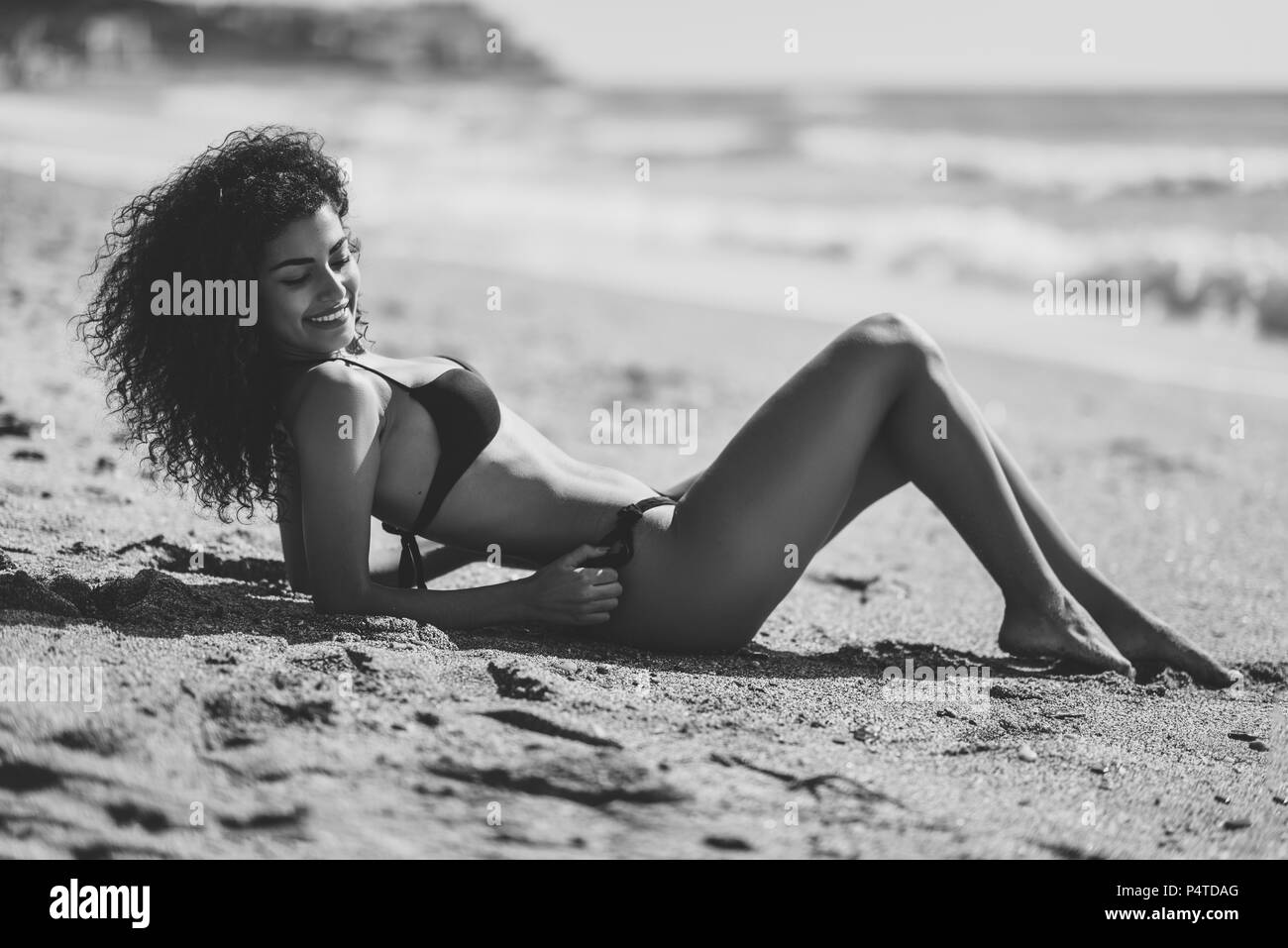 Young arabic woman with beautiful body in swimwear lying on the beach sand. Smiling female with curly long hairstyle wearing black bikini. - Stock Image