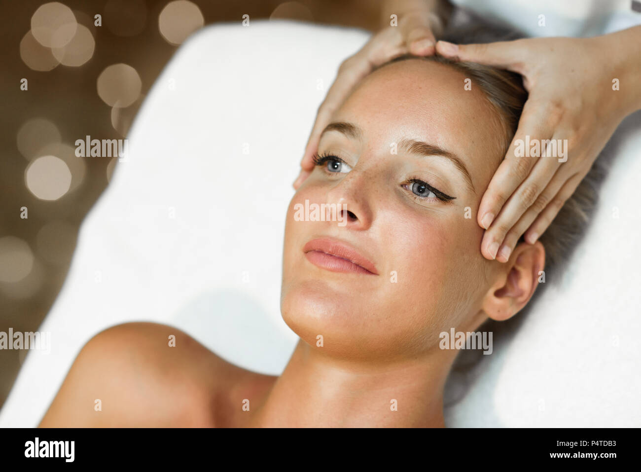 Young blond woman receiving a head massage in a spa center with blue eyes. Female patient is receiving treatment by professional therapist. - Stock Image