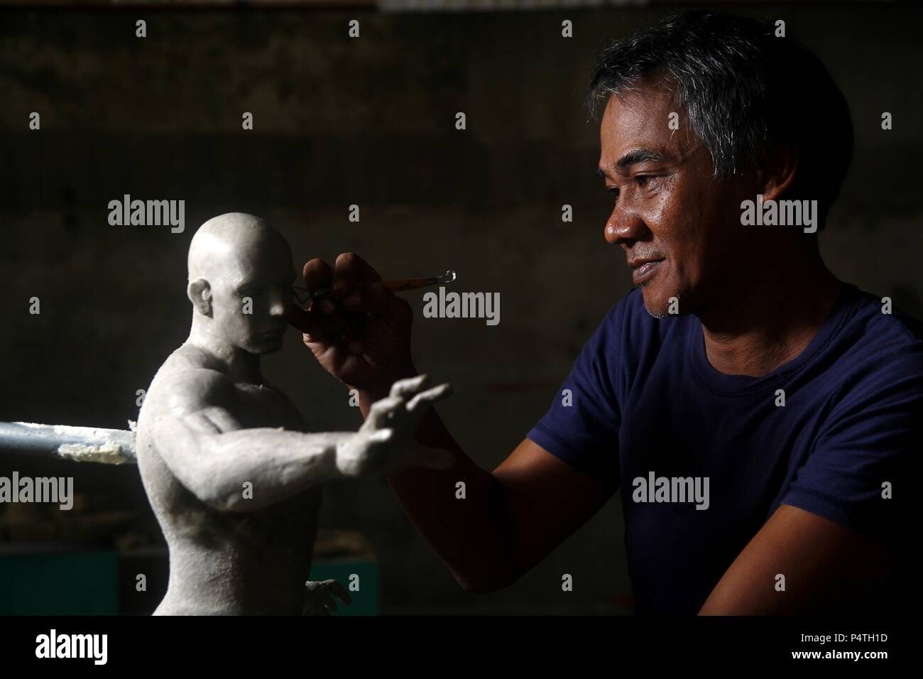 Photo of a sculptor working on a statue - Stock Image