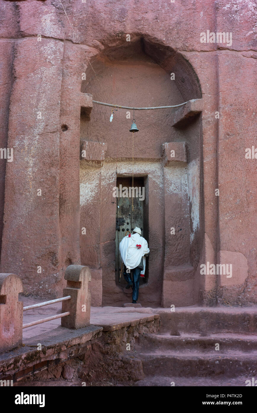 A person enters the House of the Angels Gabriel and Raphael, one of Lalibela's rock-cut churches. - Stock Image