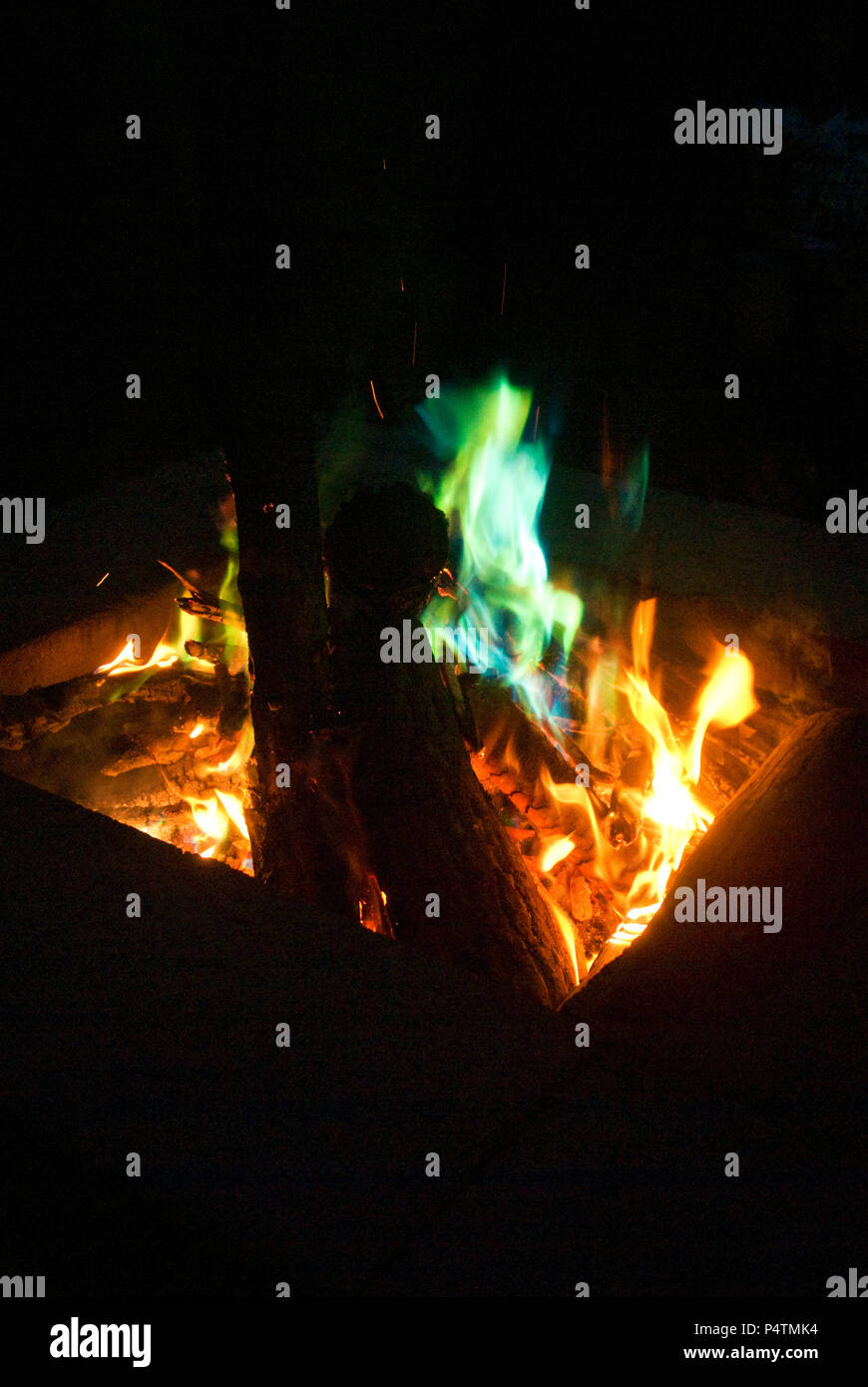 Green Flames wrap around logs inside a campfire - Stock Image