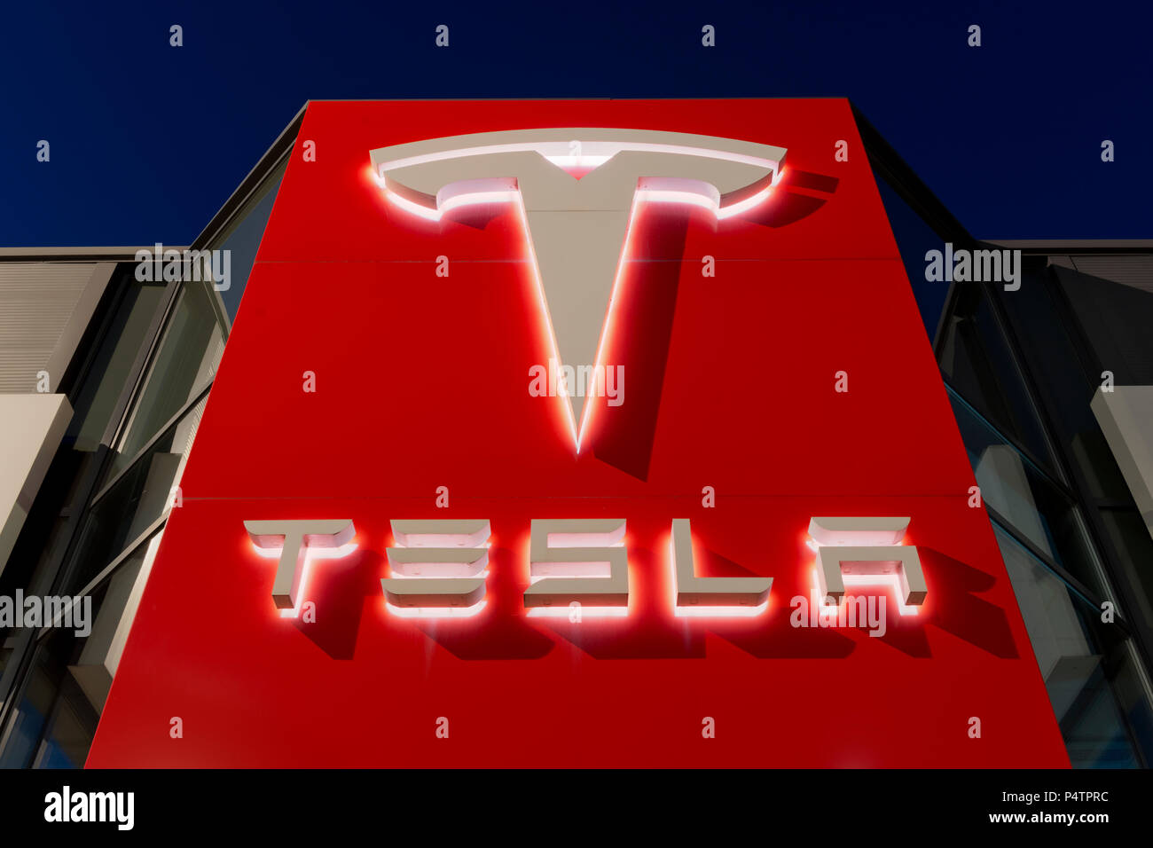 Signage for the Tesla motor company at nigtht outside one of its showrooms in South Manchester, UK. - Stock Image