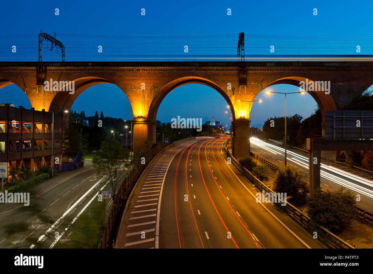The M60 motorway runs below the Stockport railway viaduct as a train passes at night. - Stock Image