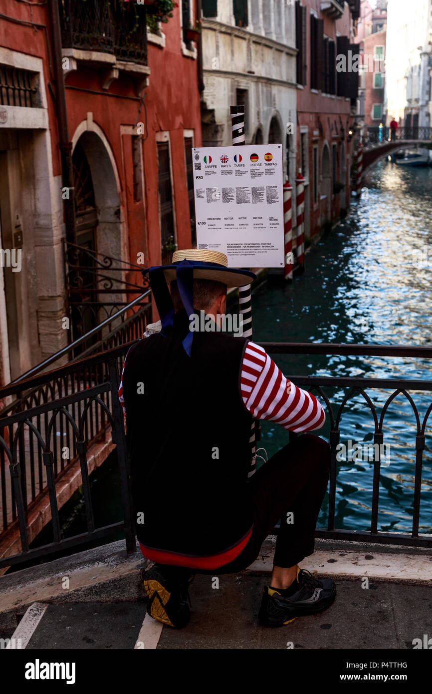 Behind a Venetian gondolier as he kneels and posts his sign to a small canal bridge, Venice, Italy - Stock Image