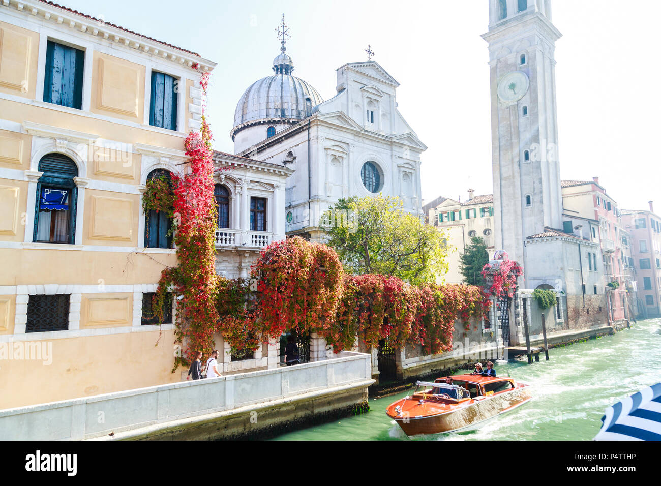 Classic motorboat with two standing tourists passing Chiesa San Giorgio (Greek Church) on Rio del Greci in bright sunshine and colors, Venice, Italy. - Stock Image