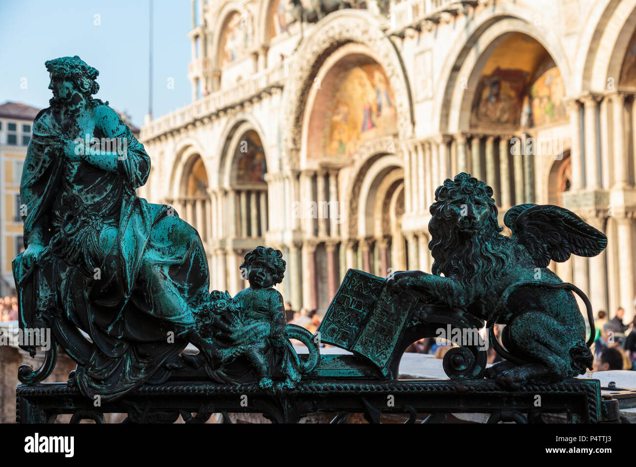 Close-up of patinated bronzes at Campanile entrance with St Marks Basilica in background, Piazza San Marco, Venice, Italy. - Stock Image