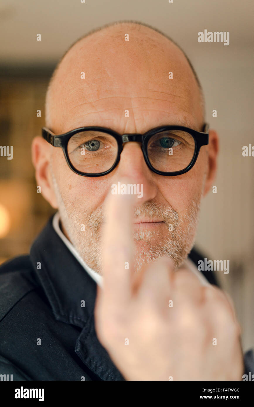 Senior man with glasses, focussing on his index finger - Stock Image