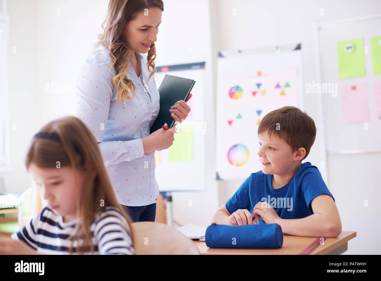 Teacher smiling at schoolboy in class - Stock Image