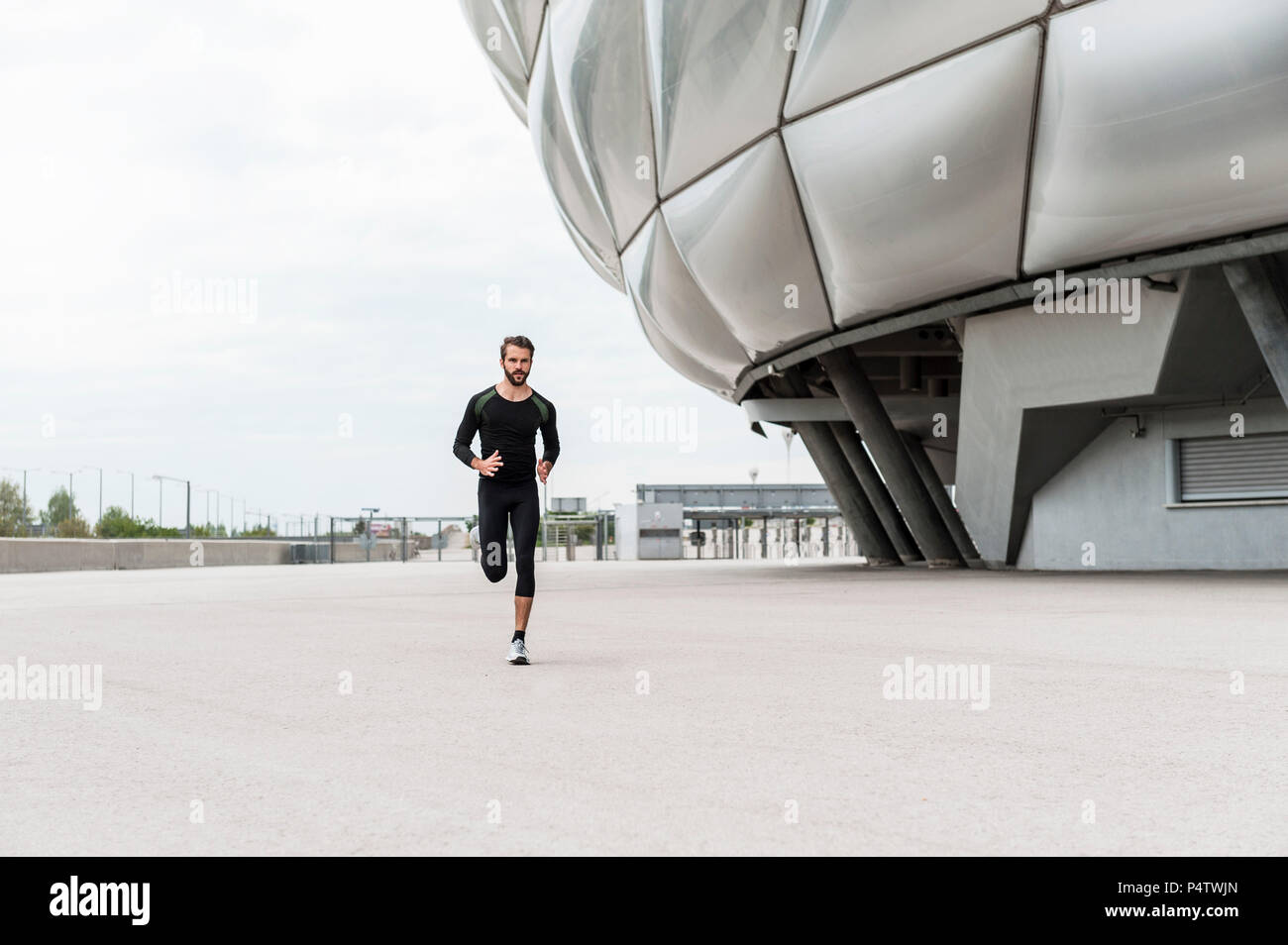 Man running at stadium - Stock Image