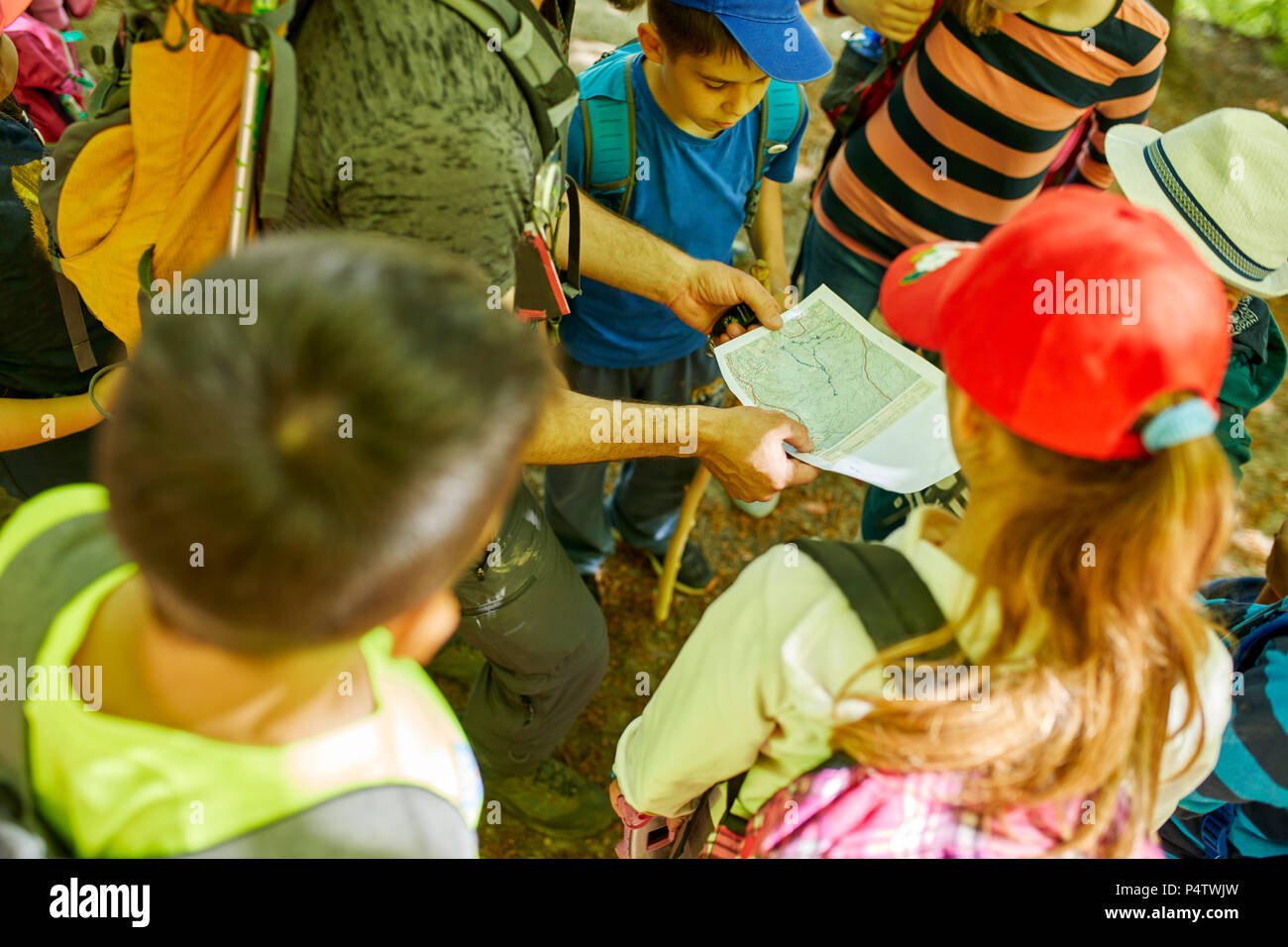 Man and kids with hiking map on a field trip Stock Photo
