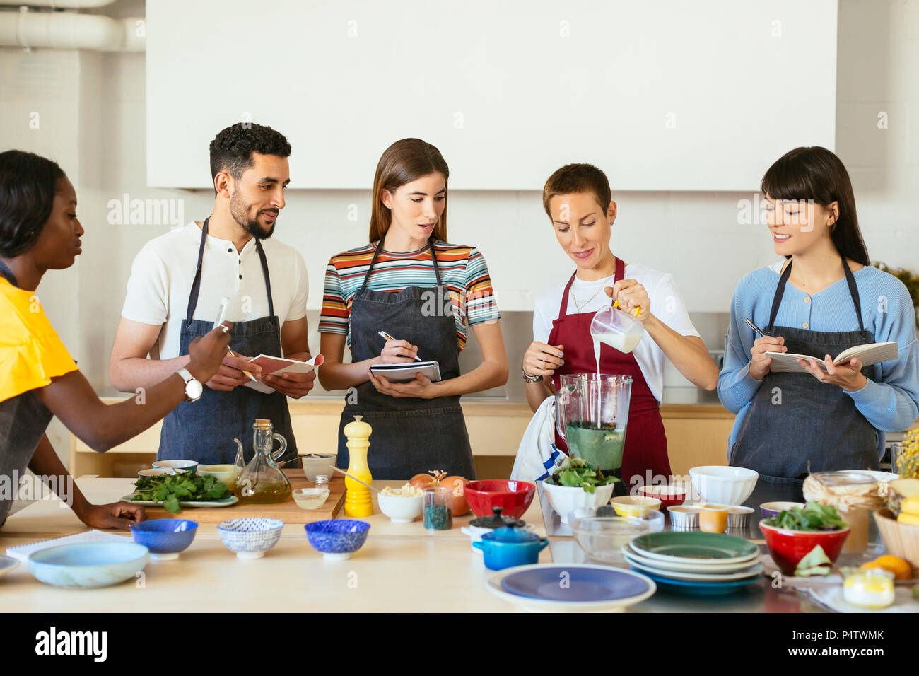 Friends and instructor in a cooking workshop preparing a smoothie - Stock Image
