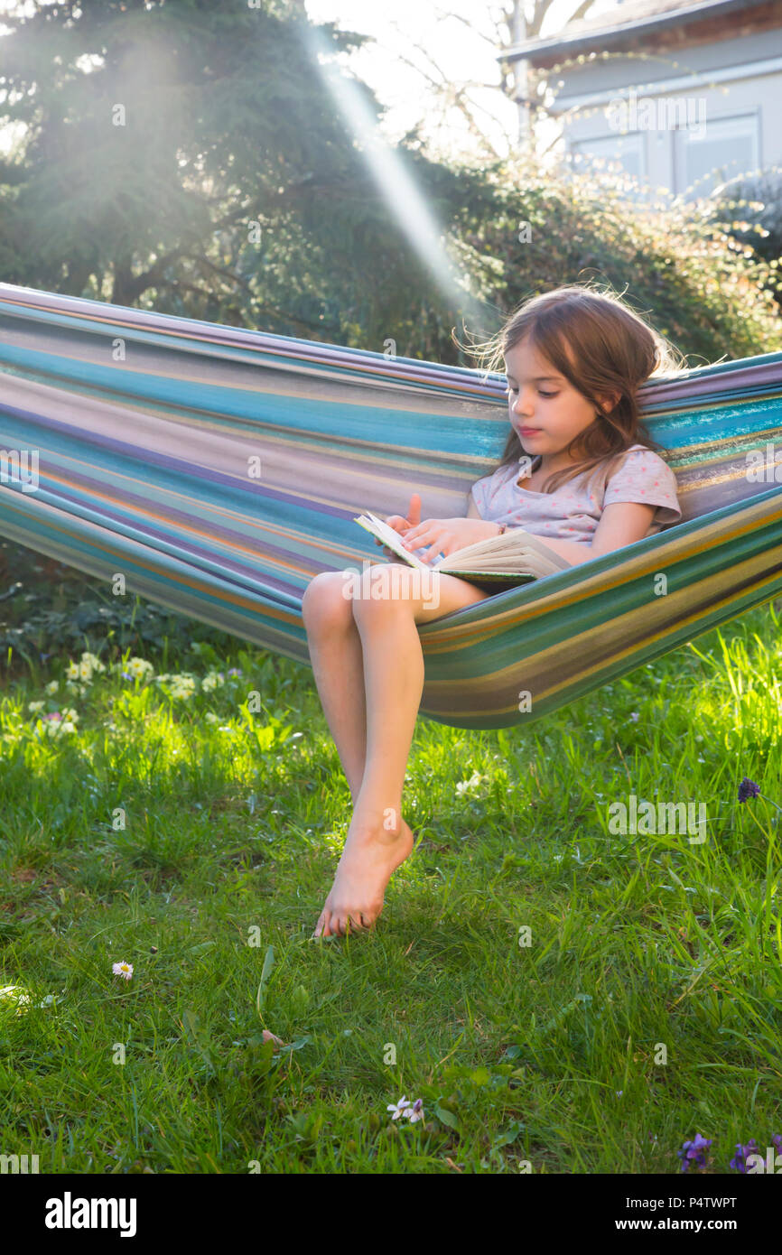 Little girl sitting on hammock in the garden reading a book - Stock Image