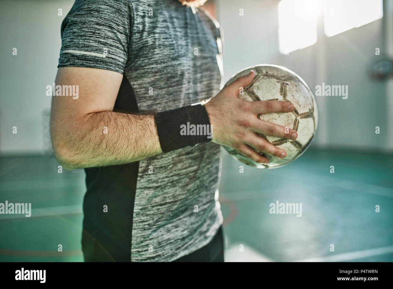 Close-up of indoor soccer player holding the ball - Stock Image
