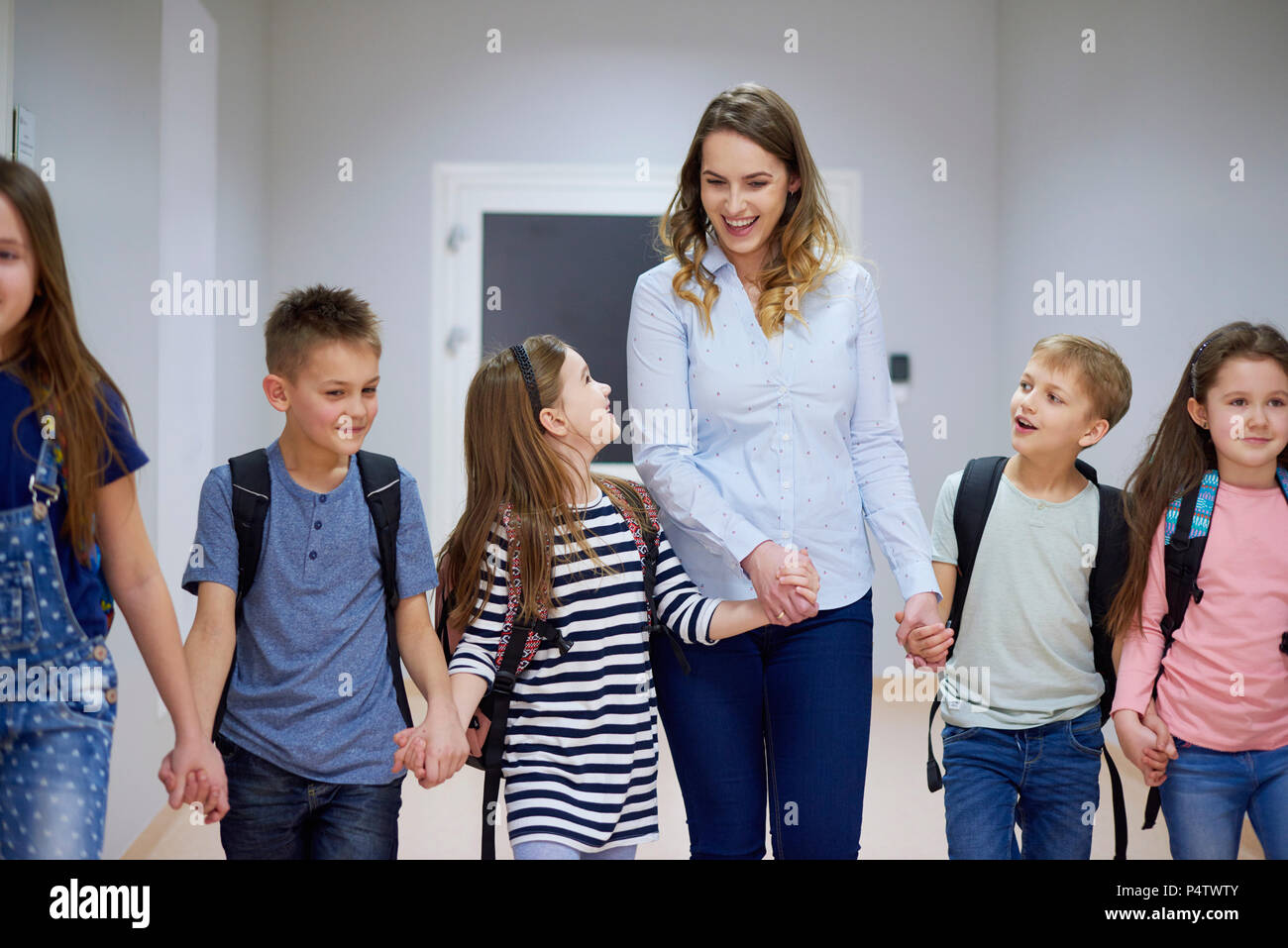 Smiling pupils and teacher walking hand in hand on corridor in school - Stock Image