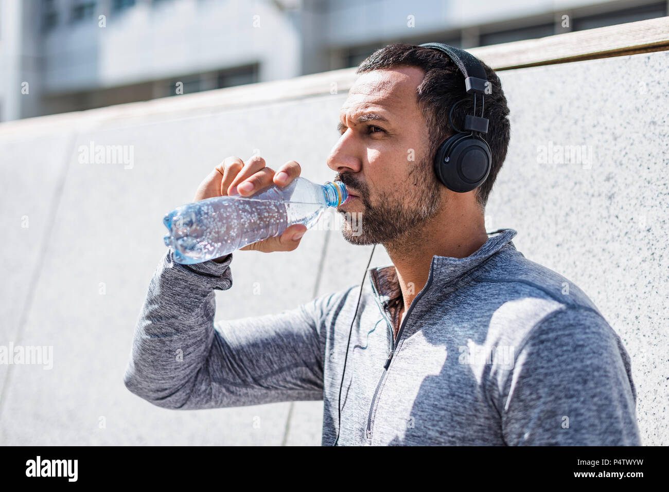 Man having a break from exercising wearing headphones and drinking from bottle - Stock Image