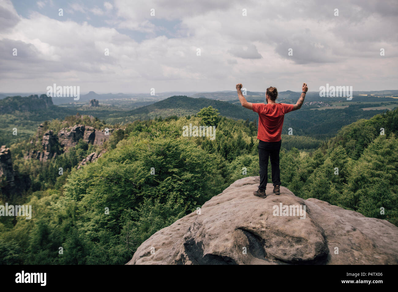 Germany, Saxony, Elbe Sandstone Mountains, man on a hiking trip standing on rock cheering Stock Photo
