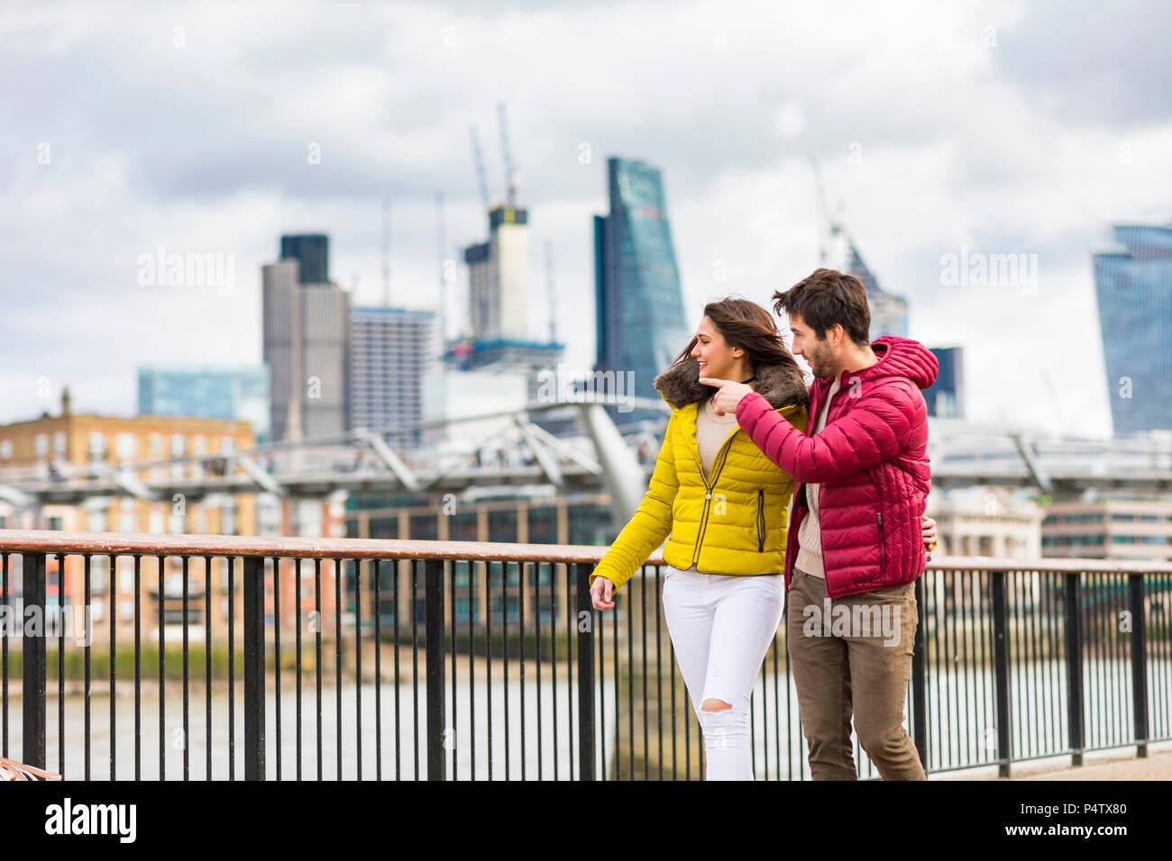 UK, London, young couple walking on bridge watching something Stock Photo