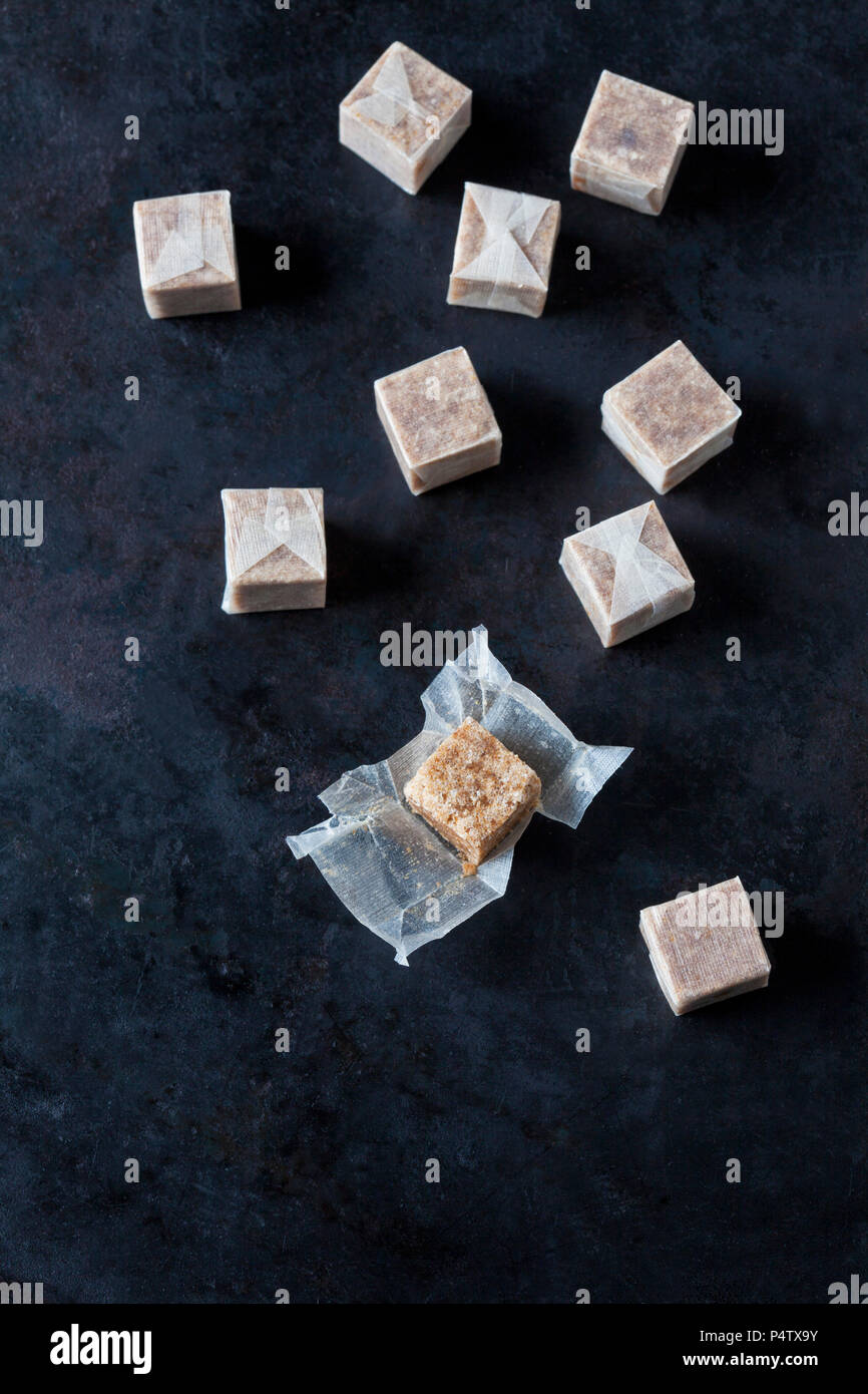 Wrapped and unwrapped stock cubes on dark ground - Stock Image