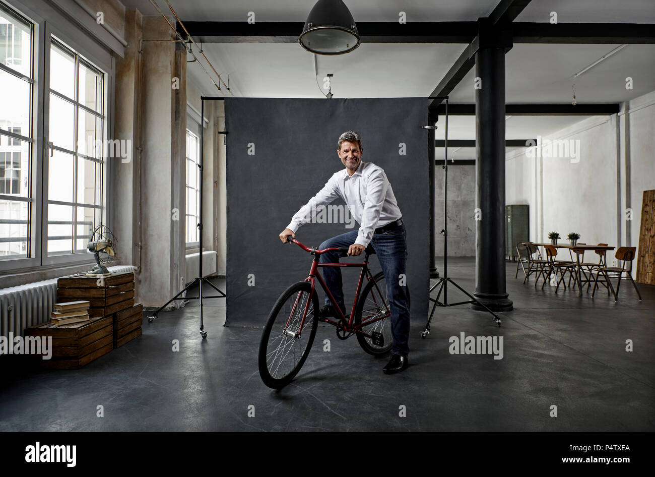 Portrait of mature businessman on fixie bike in front of black backdrop in loft - Stock Image
