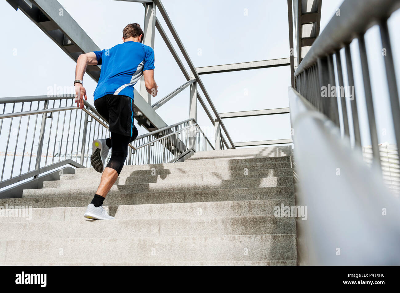 Man running up stairs - Stock Image