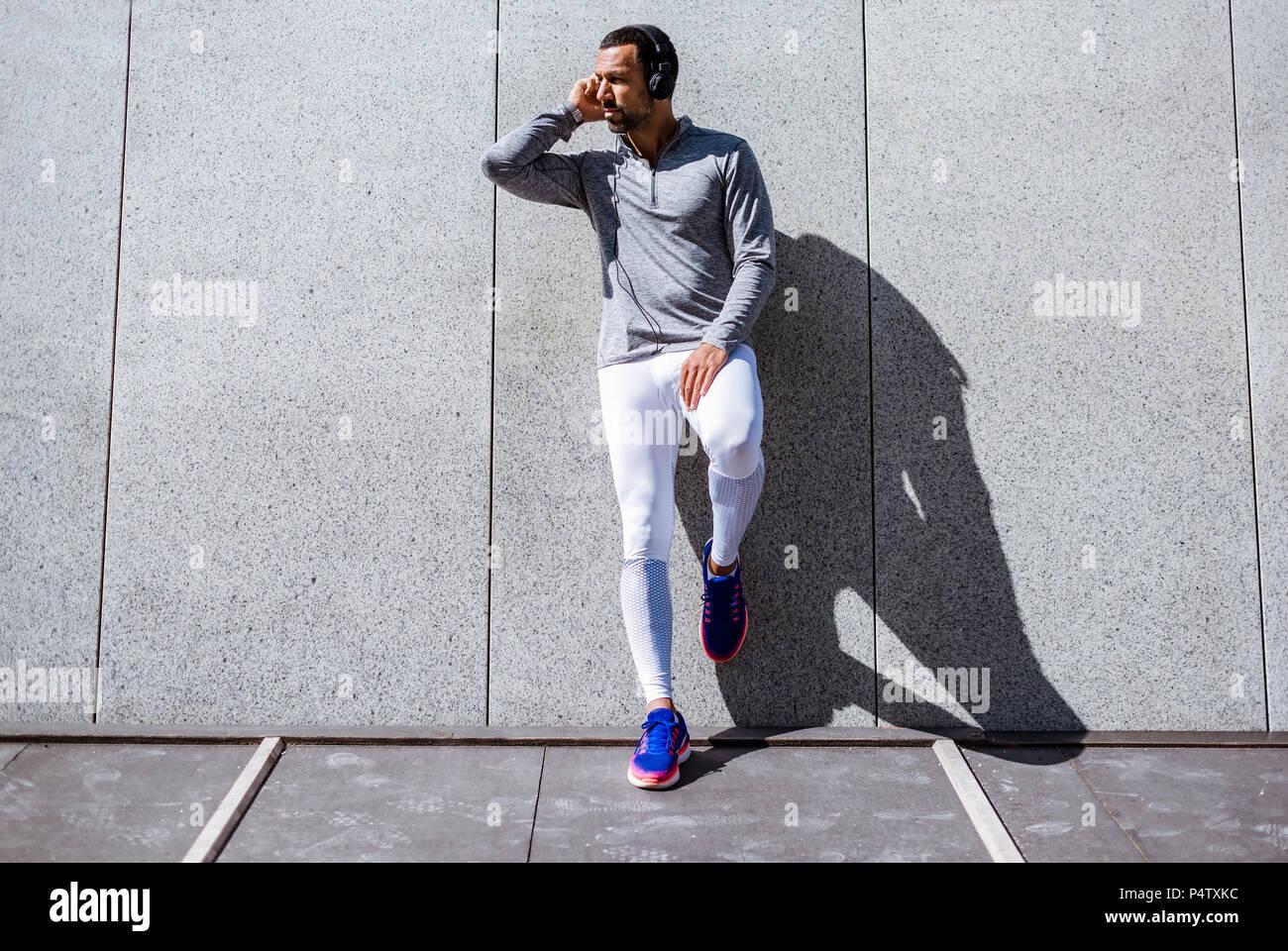 Man having a break from exercising wearing headphones - Stock Image