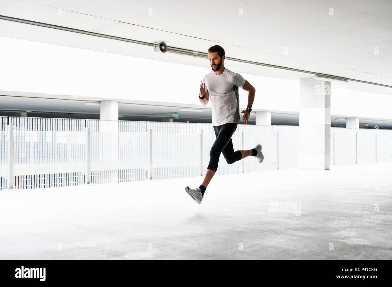 Man running in parking garage - Stock Image
