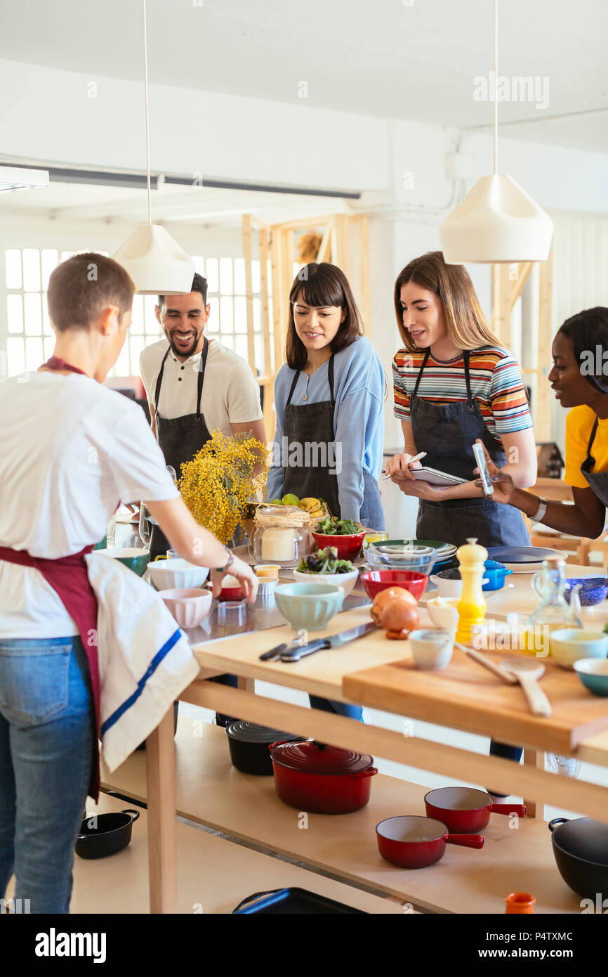 Friends in a cooking workshop watching instructor - Stock Image