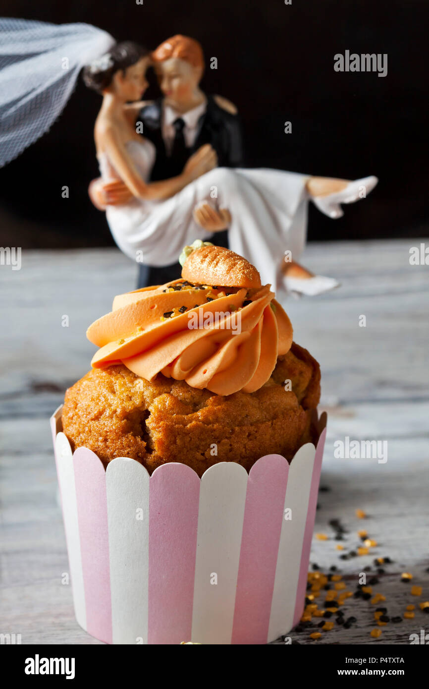 Carrot cup cake garnished with  cream topping, sugar granules and marzipan carrot - Stock Image